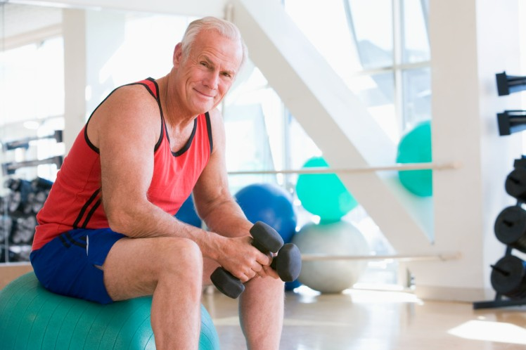 man-using-hand-weights-on-swiss-ball-at-gym